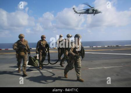 Reconnaissance Marines with the 31st Marine Expeditionary Unit's Amphibious Reconnaissance Platoon carry a fast rope during Visit, Board, Search and Seizure training aboard the amphibious assault ship USS Wasp (LHD 1), while underway in the South China Sea, Sept. 29, 2018. During the training, ARP Marines refined their fast rope capabilities while Marines with the Security Platoon held aerial security to help simulate a VBSS mission. The 31st MEU, the Marine Corps' only continuously forward-deployed MEU, provides a flexible force ready to perform a wide-range of military operations in the Indo - Stock Photo