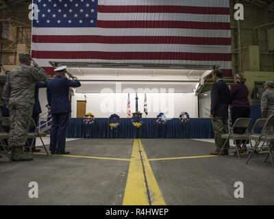 Joint Base Elmendorf-Richardson service members salute during a POW/MIA recognition ceremony at Hangar 1, JBER, Alaska, Sept. 21, 2018. POW/MIA recognition day is observed every year on the third Friday in September and honors those who were prisoners of war and those who are still missing in action. - Stock Photo