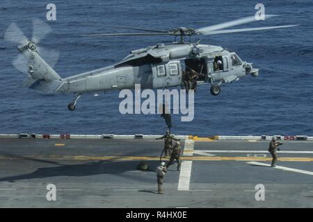 Marines with the 31st Marine Expeditionary Unit's Amphibious Reconnaissance Platoon fast-rope from an MH-60S Seahawk during Visit, Board, Search and Seizure training aboard the amphibious assault ship USS Wasp (LHD 1), underway in the South China Sea, Sept. 29, 2018. During the training, ARP Marines refined their fast rope capabilities while Marines with the Security Platoon held aerial security as part of a simulated VBSS mission. The 31st MEU, the Marine Corps' only continuously forward-deployed MEU, provides a flexible force ready to perform a wide-range of military operations. - Stock Photo