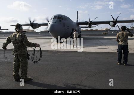 Airmen assigned to the 75th Expeditionary Airlift Squadron observe engine start up in preparation for a mission at Camp Lemonnier, Djibouti, Sept. 29, 2018. The 75th EAS supports Combined Joint Task Force - Horn of Africa with medical evacuations, disaster relief, humanitarian and airdrop operations. - Stock Photo