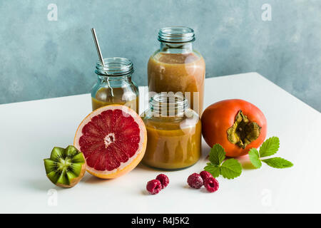different glasses with freshly made grapefruit, kiwi, persimmon and raspberry smoothies. on white table and blue background. healthy food. morning bre