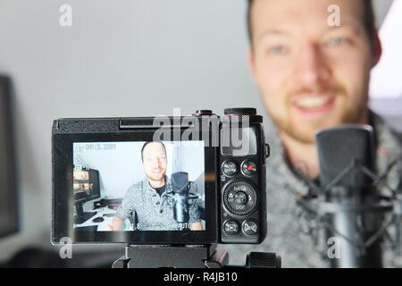 Camera display showing young male filming himself podcast content creator - Stock Photo