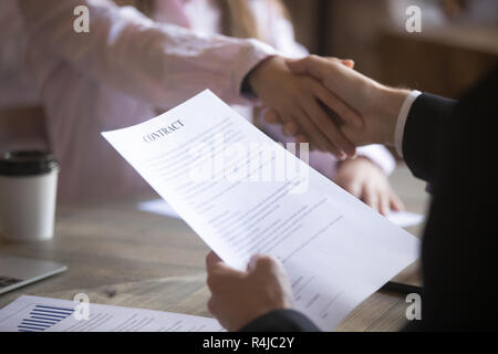 Business partners handshaking after signing a contract. - Stock Photo