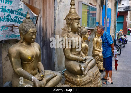 Outside a factory for Buddha statues in Bamrung Muang Road in Bangkok, Thailand, a man looks inensely at a statue placed outside for delivery - Stock Photo