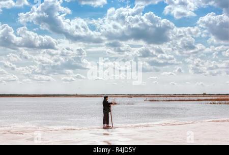 Man By The Lake Among Quartz Sand Under Beautiful Cloudy Sky - Stock Photo