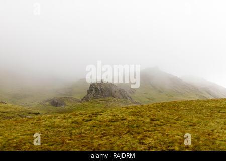 Fog over Old Man of Storr on Isle of Skye, Scotland - Stock Photo