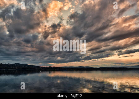 dark clouds at the sunset over the lake of Varese in a quiet autumn landscape with hills at the horizon - Stock Photo