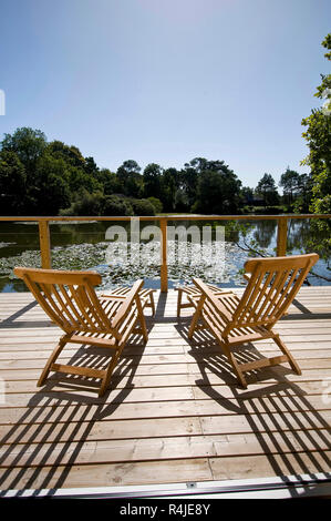 Steamer deck chairs on a decking overlooking a small lake, backlit in sunlight, clear blue sky. - Stock Photo