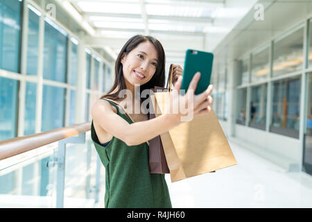 Young woman taking selfie with shopping bag - Stock Photo