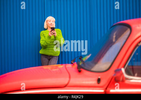 Fashion coloured concept image with blonde caucasian girl standing near a red vintage old car with blue steel wall in backgorund. Urban and colors wit - Stock Photo