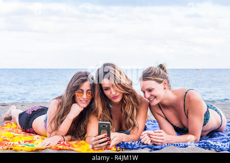 group of three beautiful girls in friendship stay lay down relaxed at the beach speaking and using a smartphone to share her summer lifestyle with fri - Stock Photo
