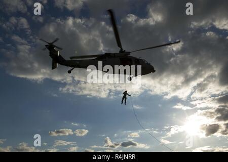 "VIRGINIA BEACH, Va. (Oct. 29, 2018) An explosive ordnance disposal technician assigned to Explosive Ordnance Disposal Group (EODGRU) 2 rappels from an MH-60S Sea Hawk helicopter assigned to the ""Chargers"" of Helicopter Sea Combat Squadron (HSC) 26 during helicopter rope suspension technique training. EODGRU 2, headquartered at Joint Expeditionary Base Little Creek-Fort Story, oversees Mobile Diving and Salvage Unit (MDSU) 2 as well as all East Coast-based Navy EOD mobile units. - Stock Photo"