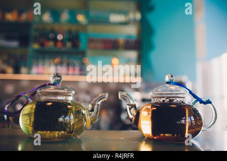 Two glass teapot half full of freshly brewed black tea. - Stock Photo