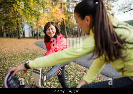 Two female runners stretching legs outdoors in park in autumn nature. - Stock Photo