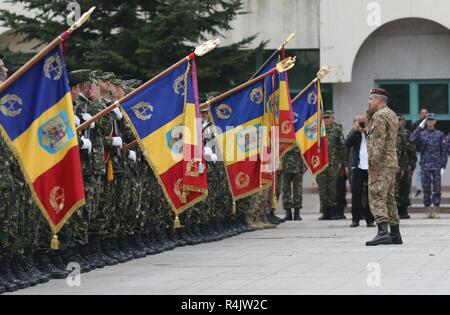 U.S., Romanian, and Canadian service members salute Romanian army Brig. Gen. Toma Dorin, commander of the Romanian Operational Army Component during the 140th anniversary of the Romanian 9th Mechanized Brigade at the House of Culture Park, Constanta, Romania, Nov. 1, 2018. The U.S. Army is committed to working with our European allies to share the responsibilities of defense by enhancing professional relationships and training. - Stock Photo