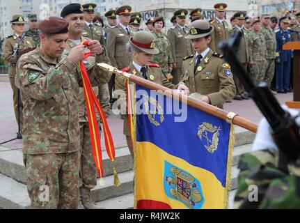 Brig. Gen. Toma Dorin, commander of the Romanian Operational Army Component, places a streamer symbolizing the Emblem of Honor of the Romanian Army on the 345th Artillery Battalion's guidon during the 140th anniversary of the Romanian 9th Mechanized Brigade at the House of Culture Park, Constanta, Romania, Nov. 1, 2018. The U.S. Army is committed to working with our European allies to share the responsibilities of common defense by enhancing professional relationships, training and operational capacity. - Stock Photo