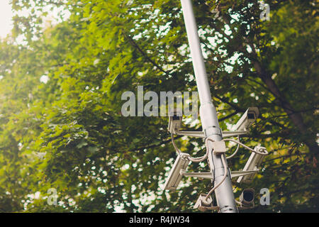 Cluster of security cameras on a lamppost in an old public Park on the background of spring foliage - Stock Photo