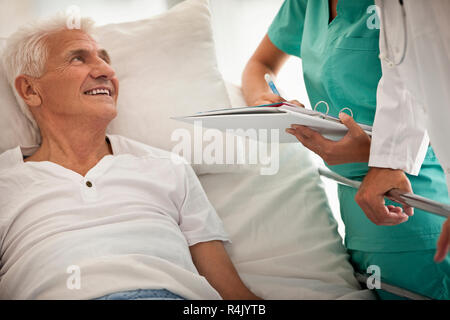 Elderly man in hospital bed,  with a doctor and nurse beside him. - Stock Photo