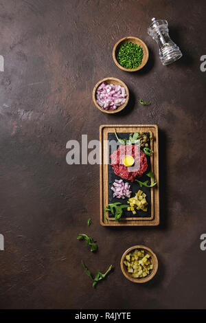 Beef tartare with quail egg in shell, cutting pickled cucumbers, capers, red onion, chives, arugula served on wooden black slate board with pepper mil - Stock Photo