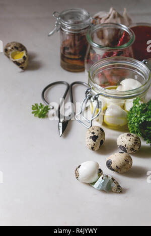 Ingredients for homemade pickled marinated quail eggs. Eggs in plastic box, tomato sauce, chili peppers, anchovies in jars, fresh greens, scissors, ol - Stock Photo