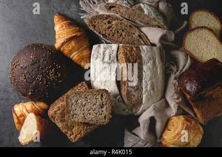 Variety of fresh baked rye, spelled, wheat craft artisan bread, whole and sliced, on cloth over black texture background. Flat lay, space - Stock Photo