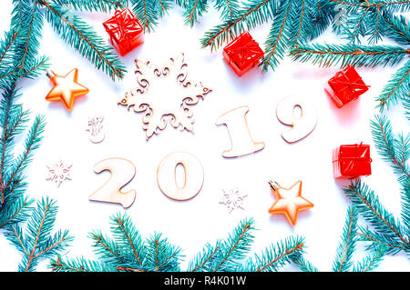 New Year 2019 background with 2019 figures, Christmas toys, blue fir tree branches. Flat lay, top view of New Year 2019 festive still life - Stock Photo