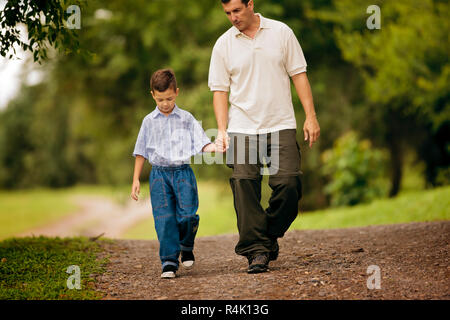 Young boy walking hand in hand with his father. - Stock Photo