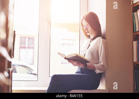 A student girl sits on a window sill in a library and reads a book - Stock Photo