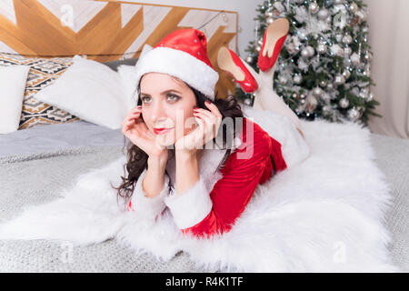 young woman in santa hat lying on the bed and dreamily looking out the window on the background of a decorated Christmas tree., home environment, waiting for Christmas. - Stock Photo