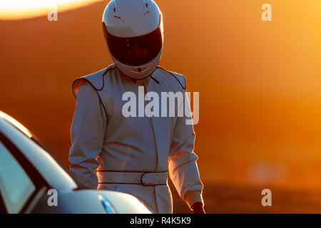 A Race Car Driver Preparing In The Early Morning Sun - Stock Photo