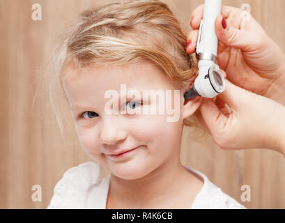 Female pediatrician examines little girl's ear. Doctor using a otoscope or auriscope to check ear canal and eardrum membrane. Child ENT check concept - Stock Photo