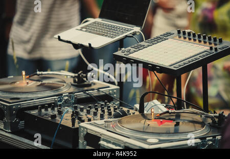 Professional dj audio setup on stage at summer open air music festival.Disc jockey equipment for playing musical tracks on party outdoor.Vinyl records - Stock Photo