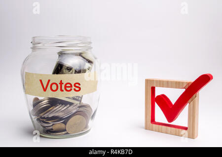 Glass jar with coins and the words Votes and a checkbox. Concept of voting for money. Bribing voters. Corruption in the electoral system. Interference - Stock Photo