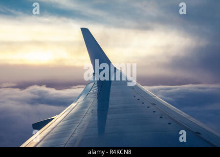 View of airplane wing from aircraft window on sunset time. Travel concept - Stock Photo