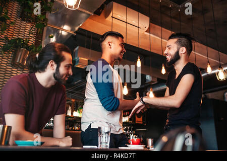 Multiracial young men meeting their friend in lounge bar. Real emotions of best friends happy to see each other. Friendship - Stock Photo