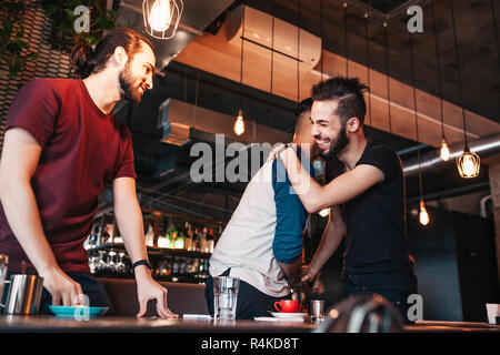 Multiracial young men meeting their friend in lounge cafe. Real emotions of best friends happy to see each other. - Stock Photo