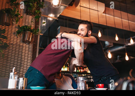Arabian young men meeting their friend in lounge cafe. Real emotions of best friends happy to see each other. - Stock Photo