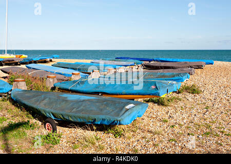Small boats lined up with protective covering on the beach at Eastbourne in East Sussex, UK - Stock Photo