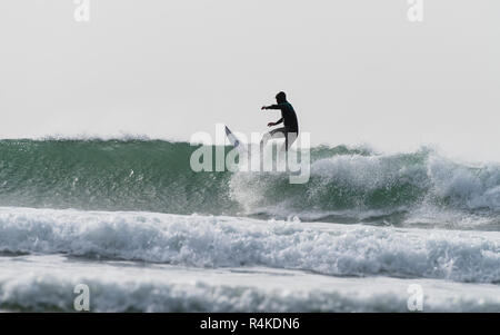 Man in wetsuit standing on a surfboard, surfing with windblown spray and green sea. - Stock Photo