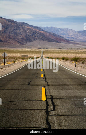 Long, straight road leading through arid landscape of Death Valley, California, USA - Stock Photo