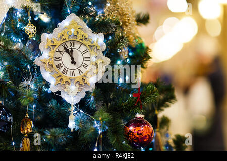 Image of decorated Christmas tree with clock, blue balls in store - Stock Photo