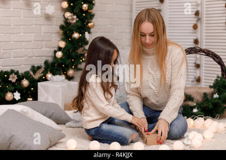mother and child girl pack Christmas gifts at home. - Stock Photo