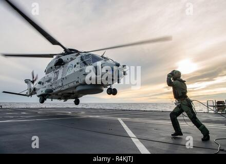 A Royal Netherlands Navy NH-90 takes off from HNLMS De Ruyter duirng NATO exercise Trident Juncture on October 31, 2018.  Trident Juncture 18 is designed to ensure that NATO forces are trained, able to operate together and ready to respond to any threat from any direction. Trident Juncture 18 takes place in Norway and the surrounding areas of the North Atlantic and the Baltic Sea, including Iceland and the airspace of Finland and Sweden. With around 50,000 participants from 31 nations, Trident Juncture 2018 is one of NATO's largest exercises in recent years. More than 250 aircraft, 65 ships an - Stock Photo