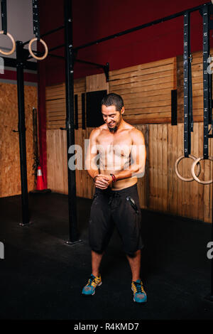 Athletic young smiling man prepares to do some cross-fit exercises without a shirt - Stock Photo