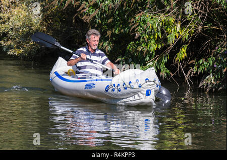 Middle aged man paddling with a double bladed paddle in a Sea Eagle SE-370 inflatable kayak, on a canal in the UK. - Stock Photo