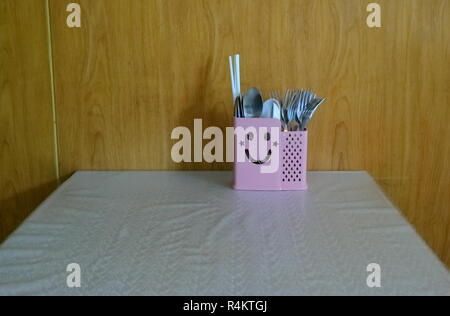 closeup of cute cutlery box with smiling face on dining table covered with tablecloth, positive thinking concept - Stock Photo