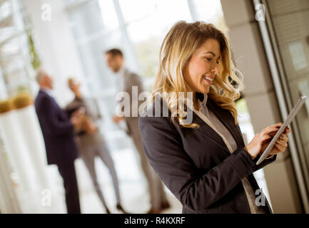 Portrait of young businesswoman using with tablet in office while other business people talking in background - Stock Photo