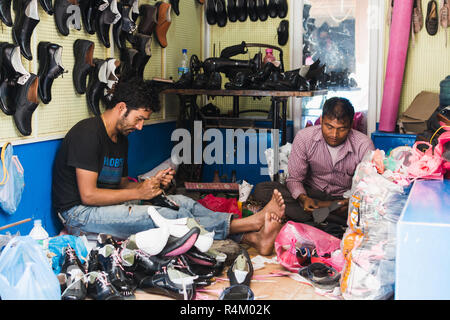 KATHMANDU, NEPAL - APRIL 2015: two shoemakers working on shoes in their workshop. - Stock Photo