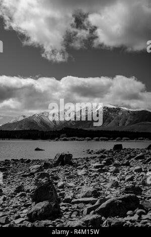 Monochrome rocky Ruataniwha Inlet foreshore at low tide with snow on top distant mountains under dramaitc clouds at Collingwood, Tasman Bay New Zealan - Stock Photo