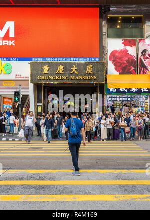Man crossing the road and people waiting at the crosswalk outside Chungking Mansions, Nathan Road, Tsim Sha Tsui, Kowloon, Hong Kong - Stock Photo
